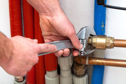 Veteran Plumbing Services with wrench turning off valves